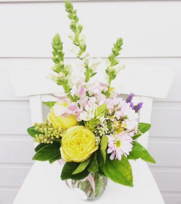 a cute jam jar arrangement in butter yellow and lilac