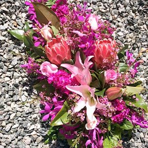 A sympathy spray arrangement in varying shades of pink