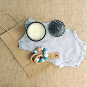 New Parent's Goodie Bag in Teal Green contains a Bear and Finn scented soy candle, a Nature Bubz teething ring and a baby body suit packaged in a craft paper bag with a bow - A Touch of Class florist Perth