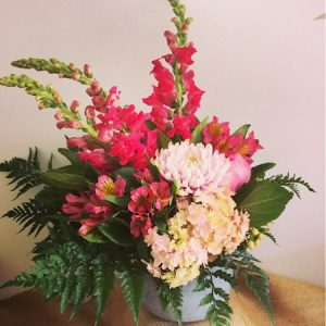 A seasonal posy style arrangement of the best blooms in pink displayed in a stylish ceramic vase.