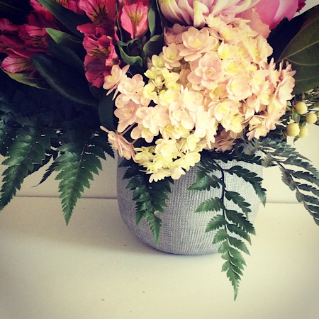 A beautiful seasonal arrangement in various shades of pink, displayed in a stylish ceramic vase.