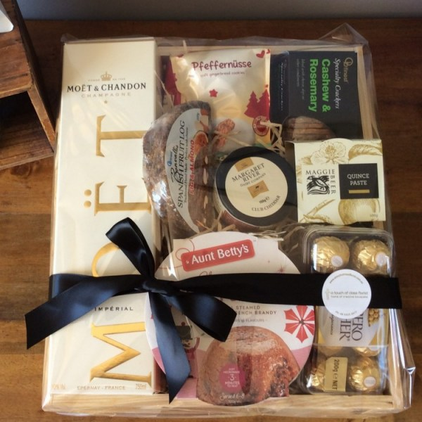 a christmas hamper of MOET champagne, cheeses, crackers and chocolates. in a wooden tray.