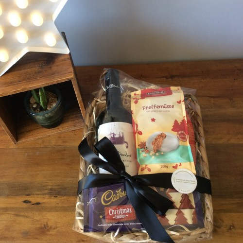 a seagrass basket filled with a bottle of red wine, a chocolate bar and ginger cookies