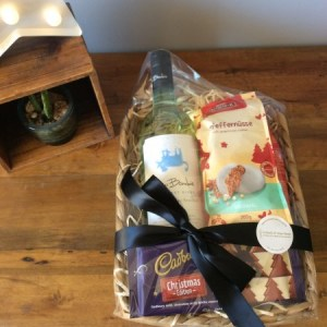 a seagrass basket filled with a bottle of white wine, a chocolate bar and ginger cookies
