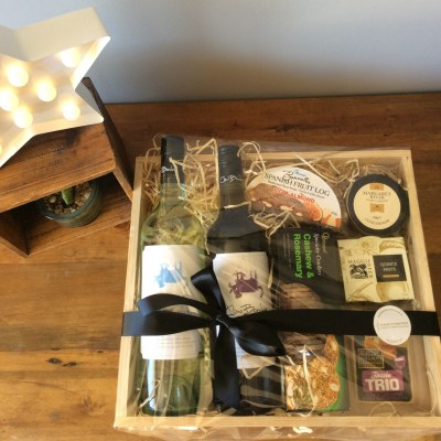 a wooden hamper tray filled with cheeses and seasonal foods.