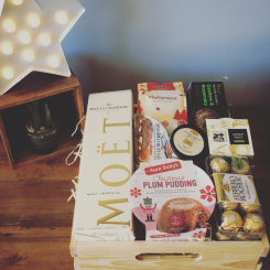 a wooden hamper tray with MOET champagne, cheese and seasonal food products