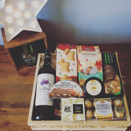 a woodden hamper tray filled with wine, cheese and seasonal foods.