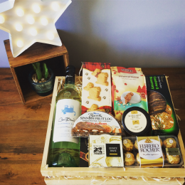 a wooden hamper tray filled with wine, cheese and seasonal foods.