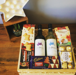 a wooden hamper tray filled with wine, and seasonal foods.