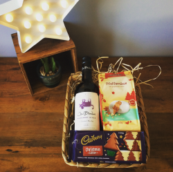 a seagrass hamper tray filled with wine and chocolates