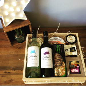 a wooden hamper tray filled with wine, cheese and food items