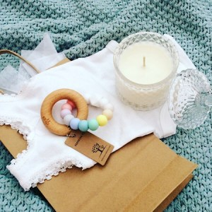 A craft bag of goodies for new parents including Bear and Finn soy scented candle, Nature Bubz teething ring in rainbow and a baby's bodysuit