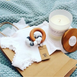 A goodie bag for parents including a Bear and Finn soy, scented candle in with a bamboo lid, a Nature Bubz teething toy in Dove Grey and a baby body suit beautifully packaged in a craft paper bag.