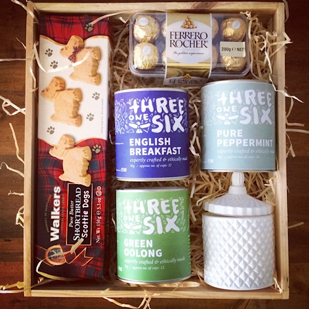 A boxed hamper with an assortment of Threeonesix tea, Ferero Rocher chocolate, shortbread and a Bear and Finn Candle
