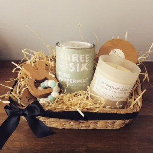 a hamper of gifts for new parents. includes a teething toy, a scented candle and a tin of tea. presented in a seagras basket.