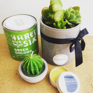 A gift hamper including a tin of tea, a mini cactus candle, some beard balm and a ceramic pot of succulents.