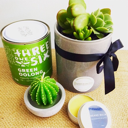 A quirky hamper including a Threesixone tea, a Possom and Blossum beard balm, a succulent pot and a small cactus candle