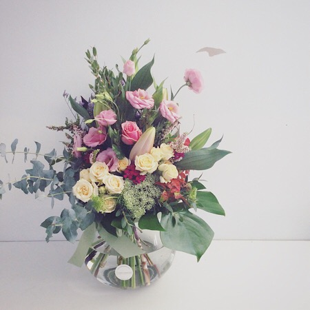 A beautiful garden style arrangement displayed in a teardop glass vase