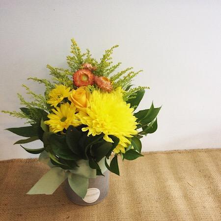 A short but cute ceramic vase arrangement in yellow