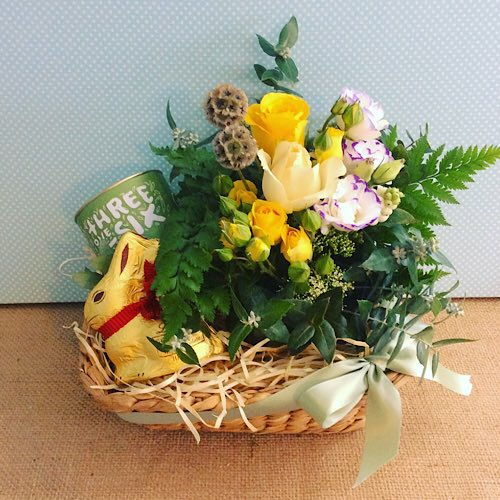 Easter Gift Hamper contains a small ceramic pot arrangement of flowers, a Lindt Chocolate Bunny and a Threeonesix tinof tea, packaged in a seagrass basket - A Touch of Class Florist