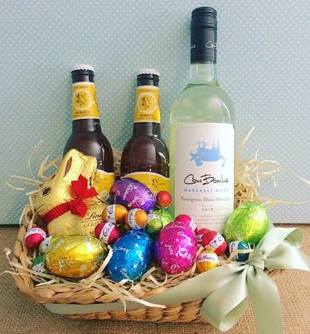 Easter Celebration Hamper contains a selection of easter eggs, a bottle of wine, and two WA beers in a seagrass basket - A Touch of Class Florist
