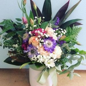 Ceramic vase arrangement in Seasonal Pastels, White ceramic vase filled with seasonal blooms in pastel shades