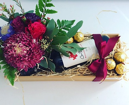 Just For You Gift Hamper includes a bottle of Red Wine, a cute desk sized flower arrangement in a ceramic jar and 6 ferrero Rocher chocolates gift wrapped in a bamboo box