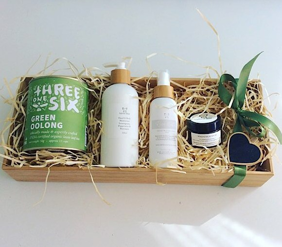 The Wellness Gift Hamper contains tea, magnesium balm, rosewater face mist and hand and body lotion gift wrapped in a bamboo box - A Touch of Class Florist Perth