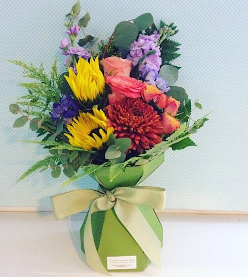 Bright Posy Box Arrangement of seasonal cheerful blooms in a card vase - A Touch of Class Florist