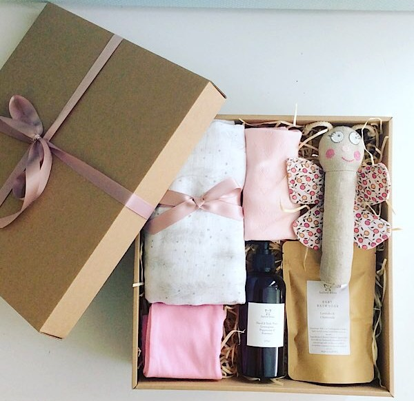 Baby Box in Pinks contains a number of baby items including clothing, a wrap, a rattle and some bath products gift wrapped in a craft box - A Touch of Class Florist Perth