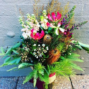 Textural vase arrangement is made up of interesting, seasonal blooms, berries, twigs and foliage.