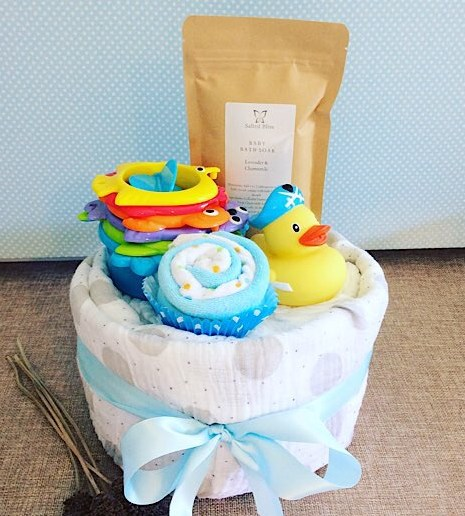 Bathtime Nappy Cake in Blue includes newborn nappies, a couple face washers and bathtime toys as well as a salted bliss baby bath wash and a baby wrap - A Touch of class florist Perth
