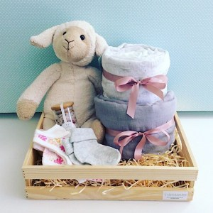 Little Lamb Baby Hamper in Pinks includes Sophie Sheep from Nana Huchy, 2 x baby wraps, newborn nappies, Sated Bliss Bath Salts, 2 items of baby clothing all wrapped up in a rustic wooden crate - A Touch of Class Florist