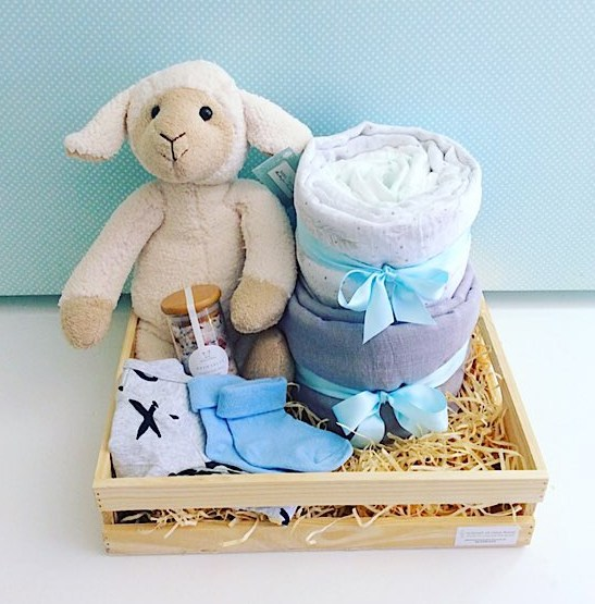 Little Lamb Baby Hamper in Blue includes Sophie Sheep from Nana Huchy, 2 x baby wraps, newborn nappies, Sated Bliss Bath Salts, 2 items of baby clothing all wrapped up in a rustic wooden crate - A Touch of Class Florist