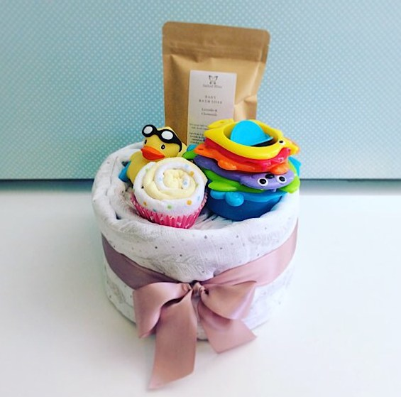 Bath Time Nappy Cake in pinks includes newborn nappies, a baby wrap, a baby bath soak from Salted Bliss, a couple of face washers and a couple of bath time toys - A Touch of Class Florist Perth