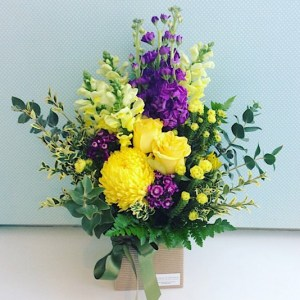 Moon River Box Arrangement includes beautiful and cheerful seasonal flowers in yellow and purple tones - A Touch of Class Florist Perth