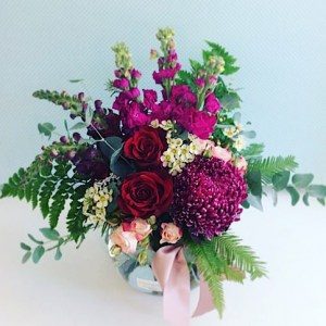 Fantasy Fishbowl Arrangement is a gorgeous glass fishbowl filled with seasonal blooms in tones of red, pink and a touch of white. A great size to sit in the middle of a table. - A Touch of Class florist Perth