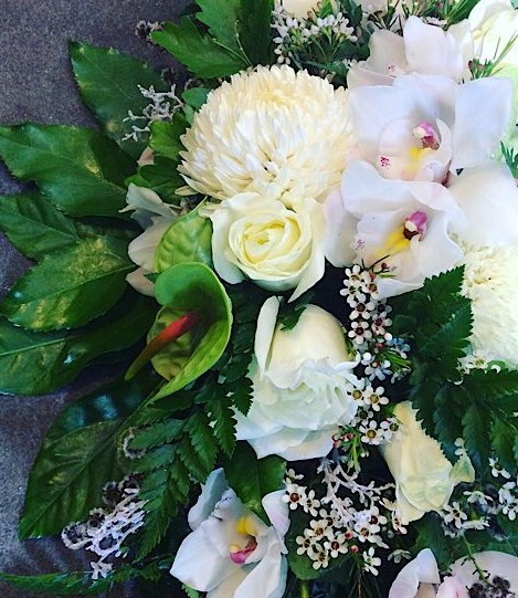 Long and low arrangement in green and white is designed to sit in the middle of a rectangular table as a floral centrepiece - A Touch of Class Florist Perth