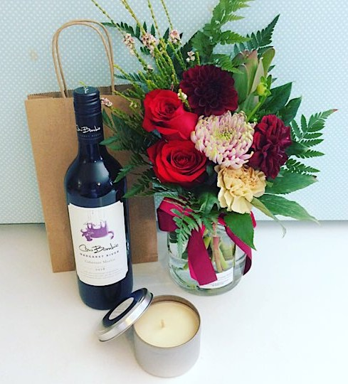 Be My Valentine? Ask the question with this cute and delightful gift combination! Includes a jam jar in romantic seasonal colours, a bottle of wine and a Bear and Finn scented soy candle in a tin - A Touch of Class Florist Perth