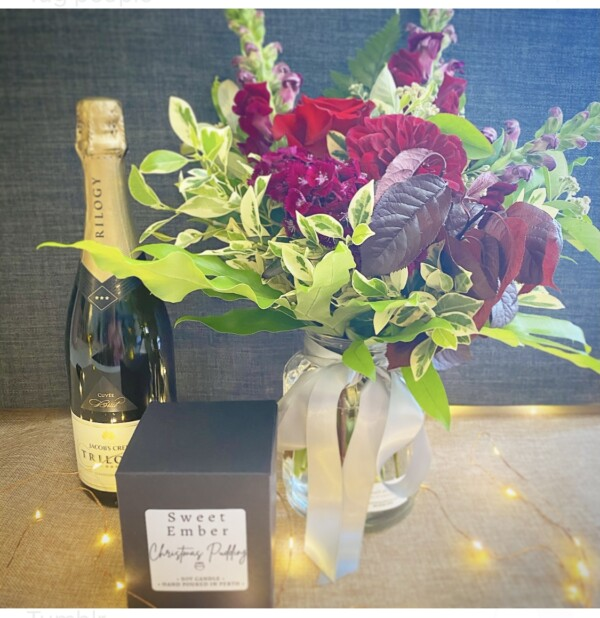 Christmas Joy Gift Selection includes a jam jar of warming red, burgundy and pink toned seasonal florals, a festive themed soy candle from Sweet Ember and a bottle of Australian sparkling wine. A Touch of Class florist Perth