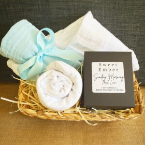 Sweetness Baby Hamper in Blue includes a couple of muslin wraps and an item of baby clothing for bubba and a sweet Ember candle for the parents, gift wrapped in a re-usable basket.